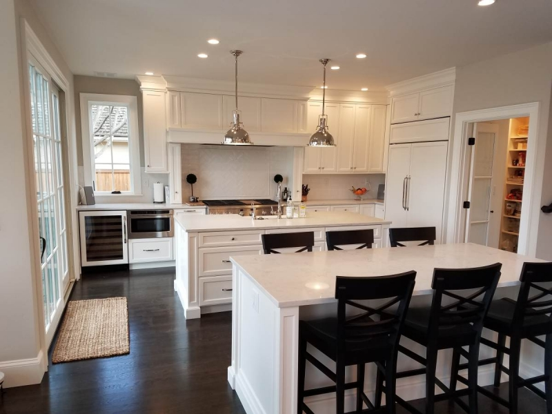 White kitchen cabinets with two islands.