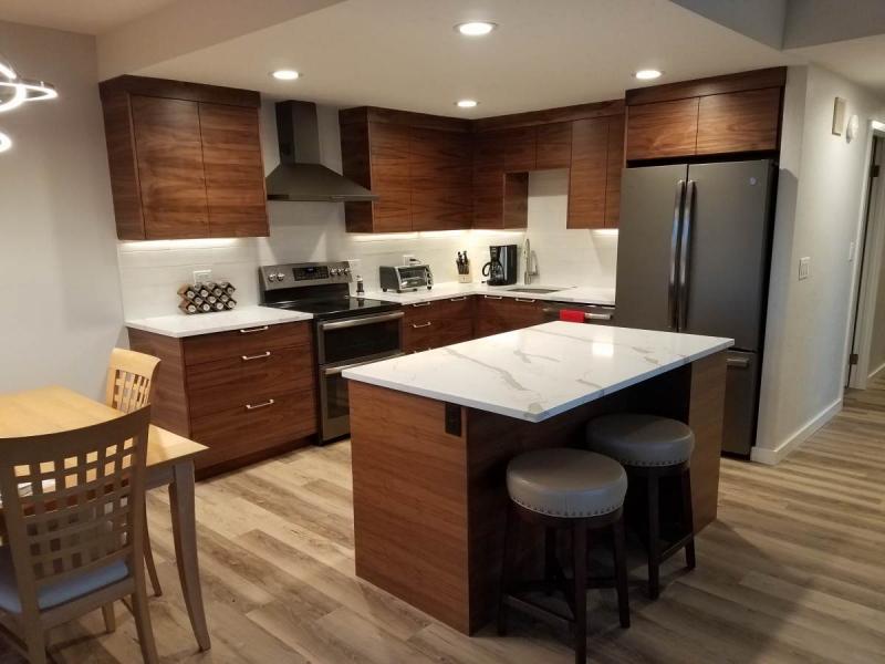 Flat panel walnut kitchen cabinetry with kitchen island.